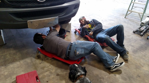 Jeff teaching Sean how to change oil.
